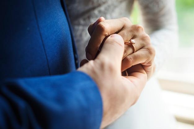 Pareja de recién casados tomados de la mano juntos