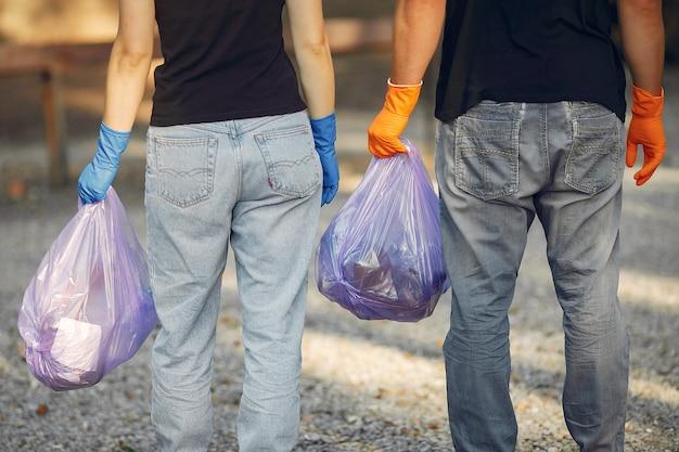 Pareja recoge basura en bolsas de basura en el parque