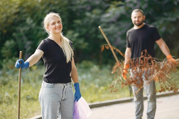Pareja recoge hojas y limpia el parque