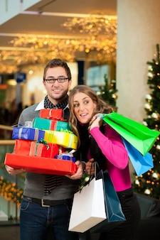 Pareja con regalos de navidad y bolsas en el centro comercial