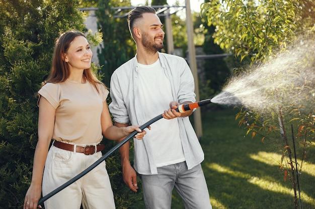 Pareja regando sus plantas en su jardín. hombre con camisa azul. la familia trabaja en un patio trasero.