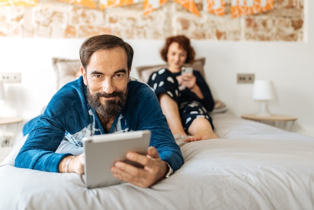 Pareja relajada en casa en la cama en el teléfono móvil y la tableta