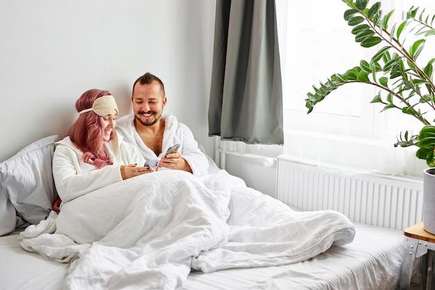 Pareja relajada usa teléfono móvil acostado en la cama juntos
