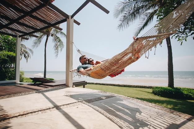 Pareja relajante en una hamaca junto a la playa