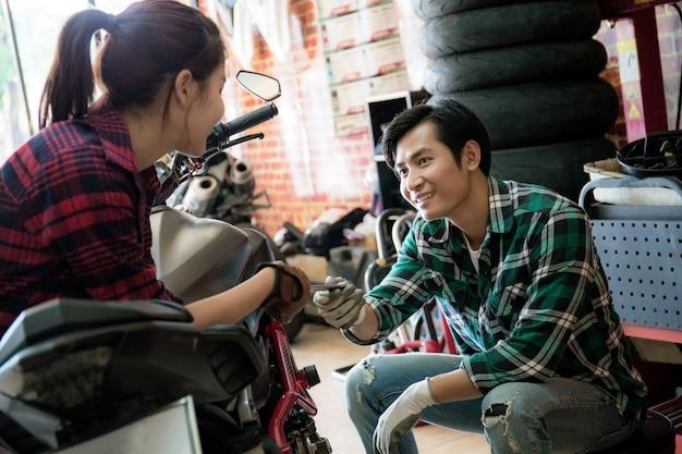 Pareja está reparando una motocicleta