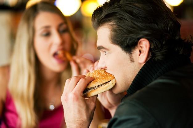 Pareja en restaurante comiendo comida rápida