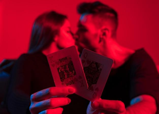 Pareja con rey y reina de corazones jugando a las cartas en las manos