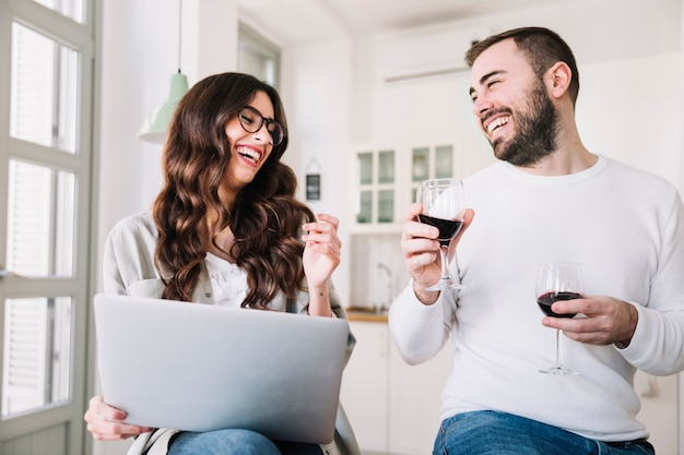 Pareja de risa con vino y portátil