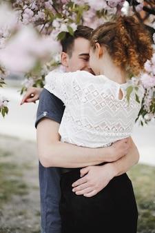 Pareja romántica abraza bajo el árbol de primavera flor