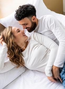 Pareja romántica abrazados en la cama en casa