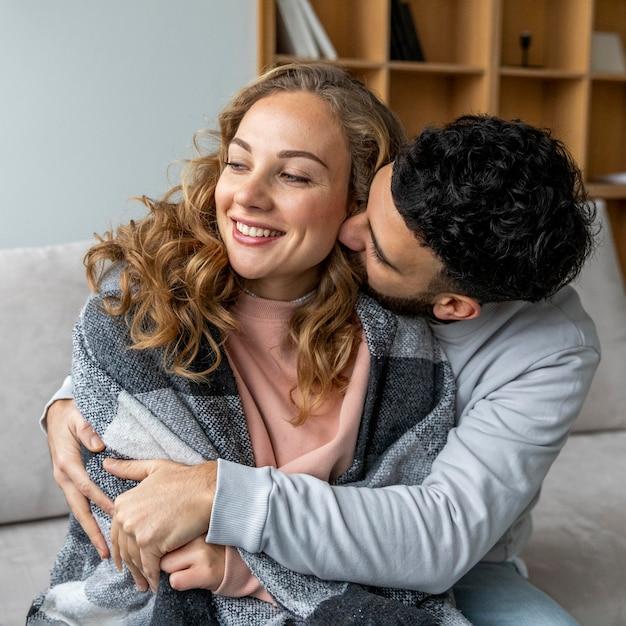 Pareja romántica abrazados en el sofá en casa
