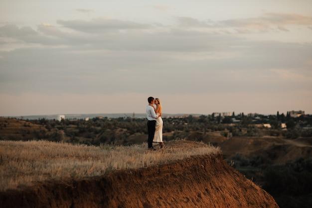 Pareja romántica de amantes abrazan y besan en el cielo colorido