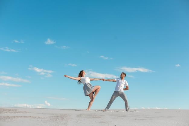 Pareja romántica bailando en el desierto de arena en el cielo azul