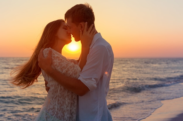 Pareja romántica besándose en la playa