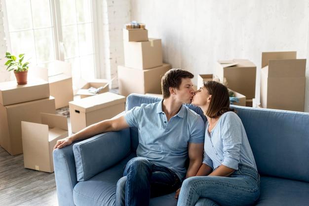 Pareja romántica besándose en el sofá mientras se prepara para mudarse