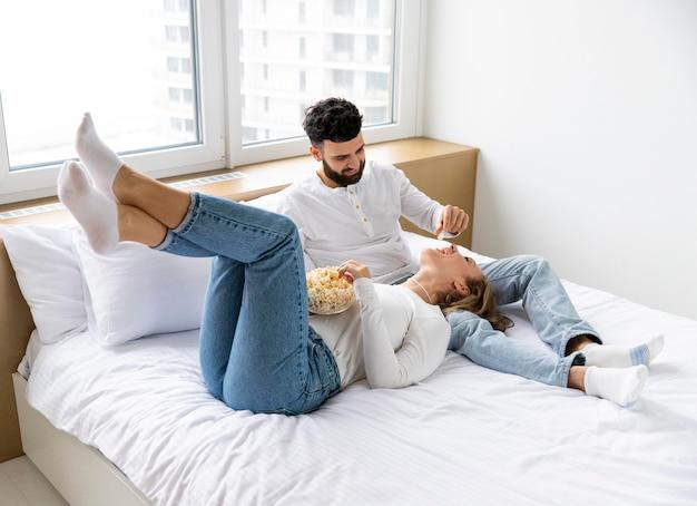 Pareja romántica en la cama en casa comiendo palomitas de maíz
