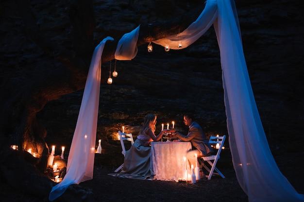 Pareja romántica cogidos de la mano juntos a la luz de las velas durante r