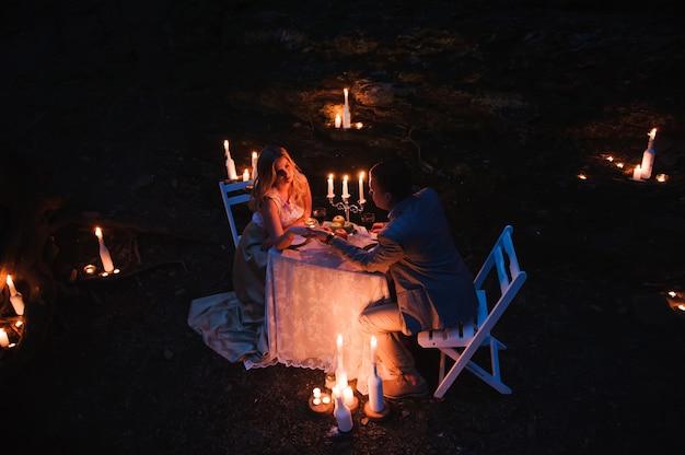 Pareja romántica cogidos de la mano juntos a la luz de las velas