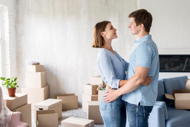Pareja romántica compartiendo un abrazo mientras empaca para mudarse de casa