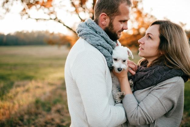Pareja romántica con divertida mascota abrazando en el campo en puesta de sol en verano.