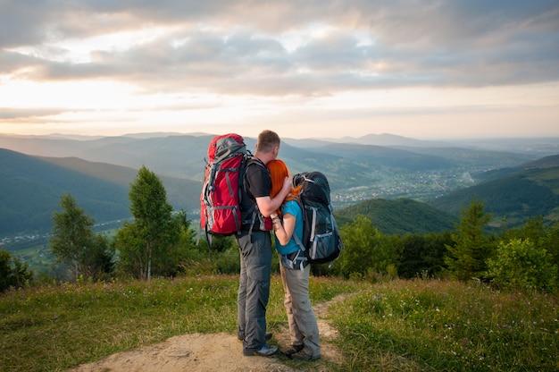 Pareja romántica excursionistas con mochilas de pie abrazando y disfrutando de la vista del hermoso mirador abierto en las montañas, bosques, colinas, pueblo en el valle y cielo nublado