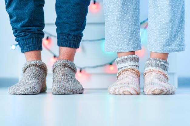 Pareja romántica de la familia de los amantes en calcetines suaves de punto cálido en invierno en casa