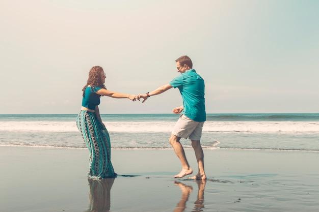 Pareja romántica feliz divirtiéndose en la playa