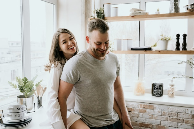 Pareja romántica joven cocinando juntos en la cocina
