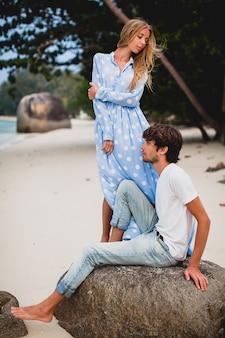 Pareja romántica joven inconformista con estilo en el amor en la playa tropical durante las vacaciones