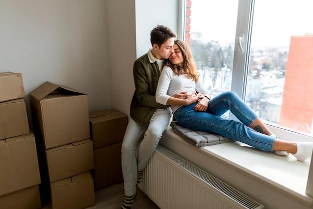 Pareja romántica joven sentada en el alféizar de la ventana en su nuevo apartamento