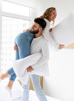 Pareja romántica lucha de almohadas en casa en la cama