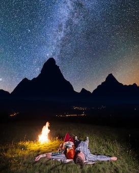 Pareja romántica mirando a las estrellas brillantes y tendida cerca de la hoguera.