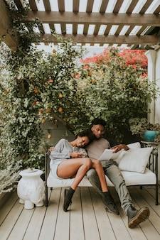 Pareja romántica negra escalofriante en el jardín con un libro