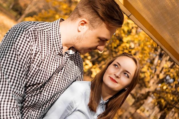 Pareja romántica en el parque de otoño - día soleado - concepto de amor, relación y citas