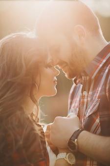 Pareja romántica de pie cara a cara cogidos de la mano en la luz del sol