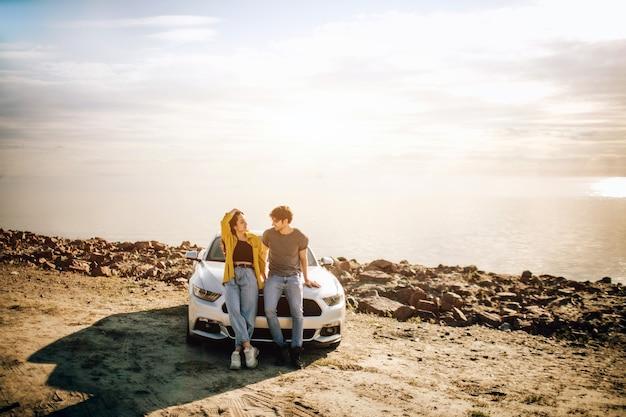Pareja romántica está de pie cerca de un muscle car en la playa. el apuesto hombre barbudo y una atractiva joven tienen una historia de amor.