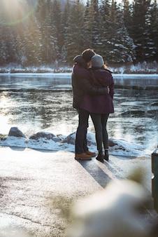 Pareja romántica de pie junto al río en invierno