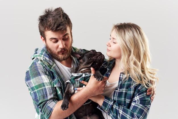 Pareja romántica en ropa casual se divierte con su perro bulldog francés en la pared blanca