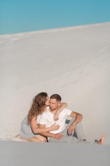 Pareja romántica sentada en arena blanca y huggins en el desierto