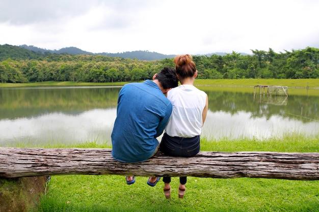 Pareja romántica sentada en la madera y disfrutando de la vista de un lago tranquilo