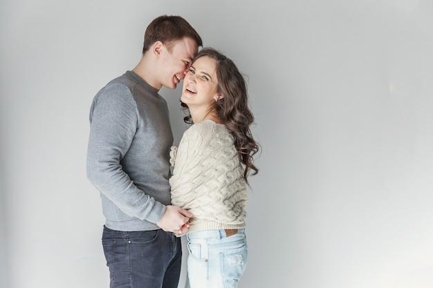 Pareja romántica sexy. mujer joven que abraza al novio en blanco