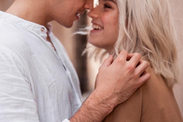 Pareja romántica sonriendo y posando afuera