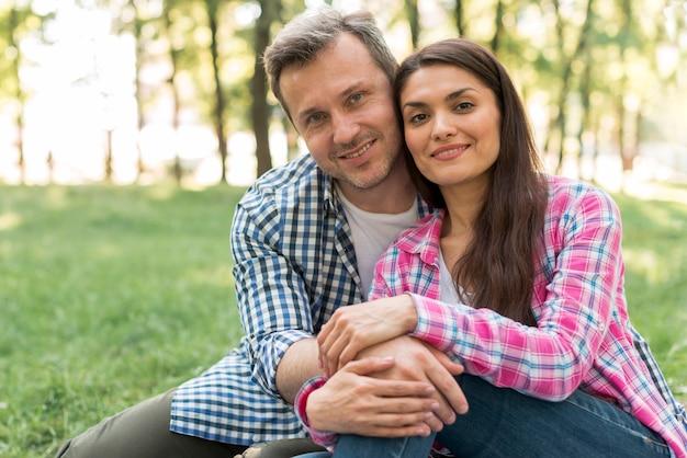Pareja romántica sonriente sentada en el parque mirando a la cámara