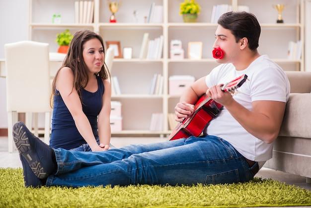 Pareja romántica tocando la guitarra en el piso