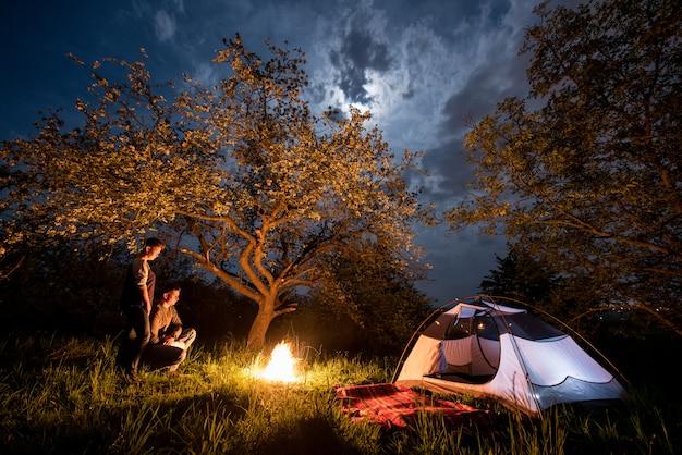 Pareja romántica turistas de pie en una fogata cerca de la tienda bajo los árboles y el cielo nocturno con la luna. camping nocturno