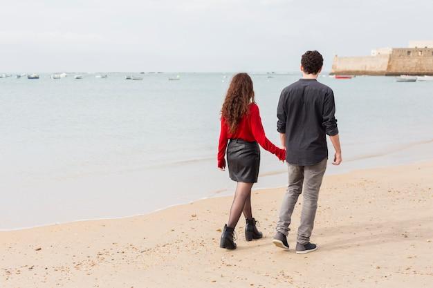 Pareja en ropa casual caminando en la orilla del mar