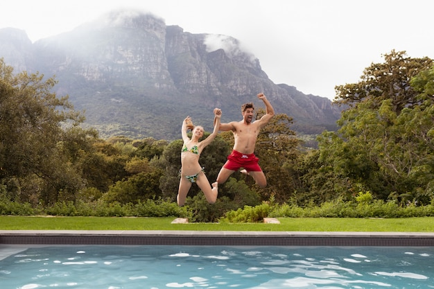 Pareja saltando juntos en la piscina