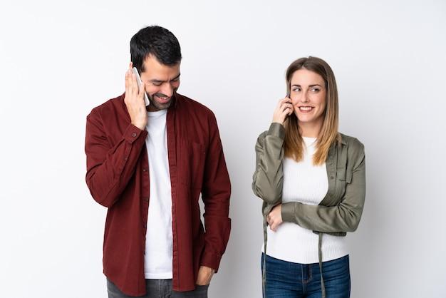 Pareja en san valentín sobre pared aislada hablando con el móvil