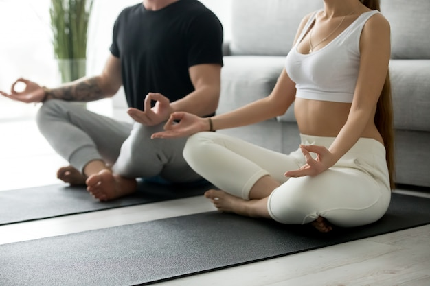 Pareja sana haciendo yoga en casa practicando meditación juntos,