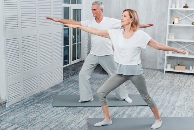 Pareja sana realizando ejercicio en estera de yoga en casa